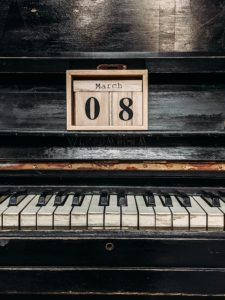 A vintage piano and calendar.